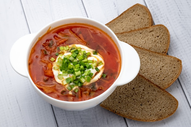 Ukrainian red borsch with sour cream in white plate and pieces of dark brown bread. russian cuisine concept. light wooden background.