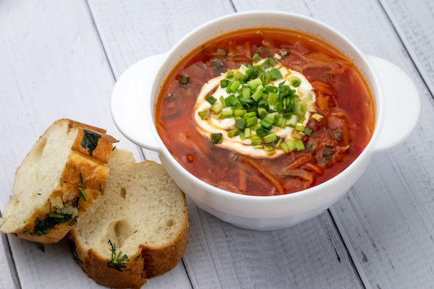 Ukrainian red borscht with sour cream in white bowl and pieces of bread with garlic. russian cuisine concept. light wooden planks background, table.