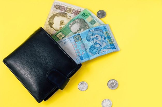 우크라이나어 작은 돈 그 리브냐와 가죽 검은 지갑에 페니.