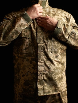 Ukrainian soldier dressed in uniform stands in the dark and fastens his jacket