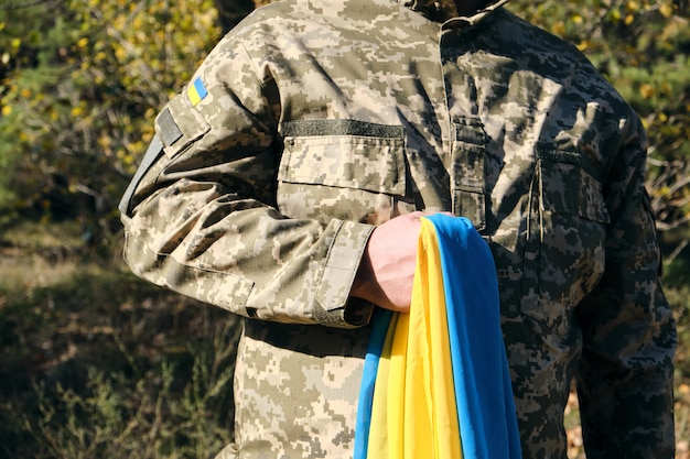 Ukrainian soldier holds in his hand the yellow-blue flag of the state, he pressed his hand to his chest