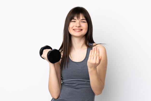 Украинская спортивная девушка делает тяжелую атлетику, изолированную на синей стене, приглашая прийти с рукой.