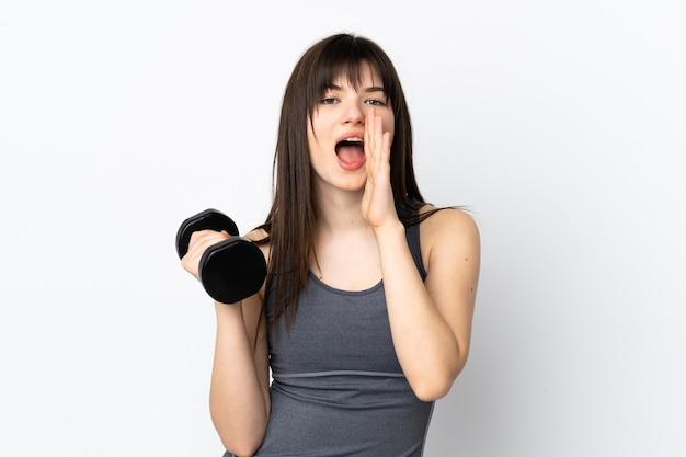 Украинская спортивная девушка делает тяжелую атлетику, изолированную на синей стене, кричит с широко открытым ртом