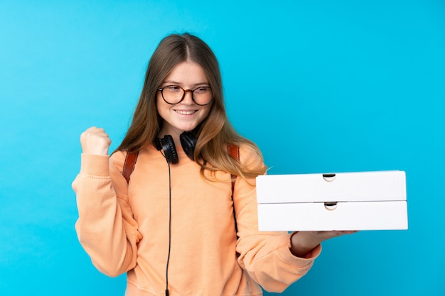 Ukrainian teenager girl holding pizzas over isolated blue wall celebrating a victory