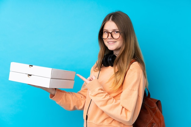 Ukrainian teenager girl holding pizzas over isolated blue wall and pointing it