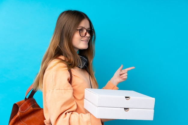 Ukrainian teenager girl holding pizzas over isolated blue wall pointing to the side to present a product
