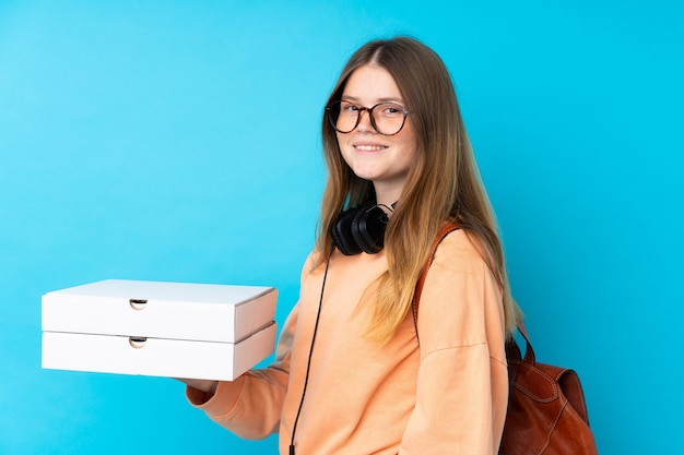 Ukrainian teenager girl holding pizzas over isolated blue wall smiling a lot