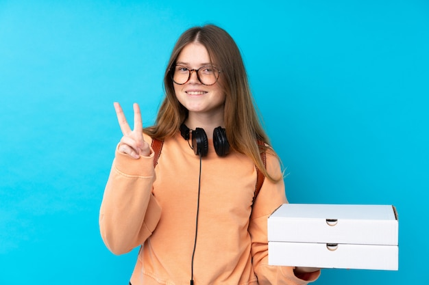 Ukrainian teenager girl holding pizzas over isolated blue wall smiling and showing victory sign