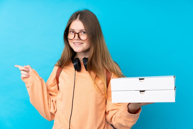 Ukrainian teenager girl holding pizzas over isolated blue wall surprised and pointing finger to the side
