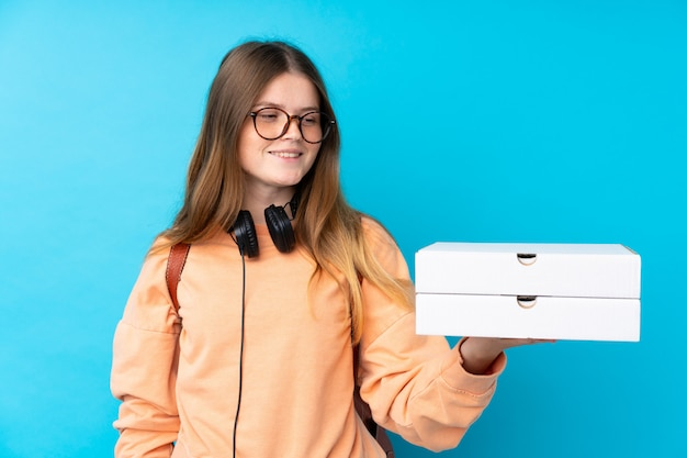 Ukrainian teenager girl holding pizzas over isolated blue wall with happy expression