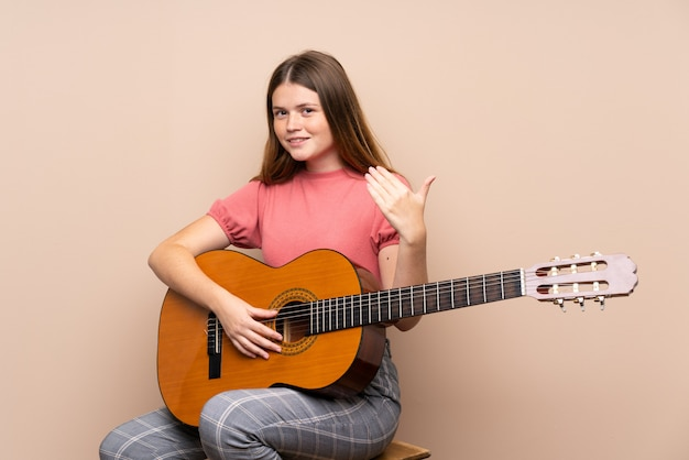 Ukrainian teenager girl with guitar inviting to come with hand. happy that you came