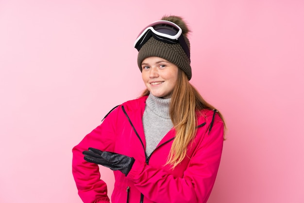 Ukrainian teenager skier girl with snowboarding glasses over isolated pink extending hands to the side for inviting to come