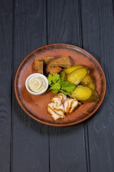 Украинская традиционная закуска из бекона, маринованных огурцов и хлеба на черной деревянной поверхности