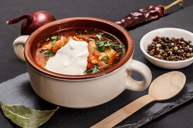 Ukrainian traditional borsch in porcelain bowl with sour cream, onion, allspices and chilli pepper on black stone board. top view.