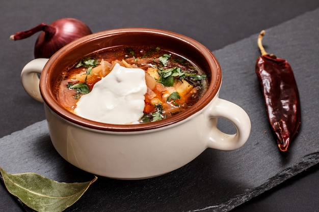 Ukrainian traditional borsch in porcelain bowl with sour cream, onion and chilli pepper on black stone board. top view.