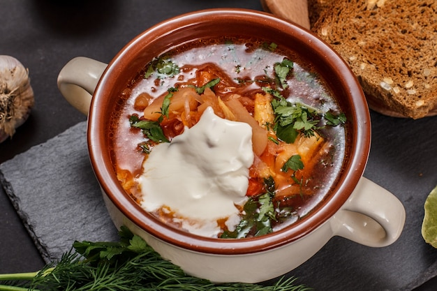 Ukrainian traditional borsch in porcelain bowl with sour cream, rye bread on black stone board. top view.
