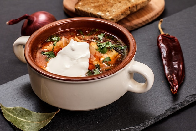 Ukrainian traditional borsch in porcelain bowl with sour cream, rye bread, onion and chilli pepper on stone board. top view.