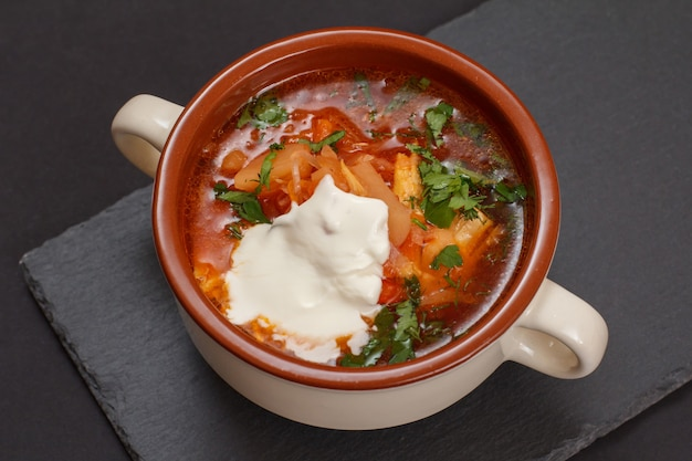Ukrainian traditional borsch with sour cream in porcelain bowl on stone board. top view.