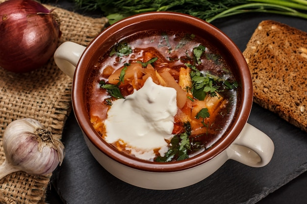 Ukrainian traditional borsch with sour cream in porcelain bowl with rye bread, parsley, onion, garlic on sackcloth and stone board. top view.
