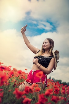 Ukrainian woman in sportswear and straw hat taking a photo selfie with smartphone in poppies field in summer day.