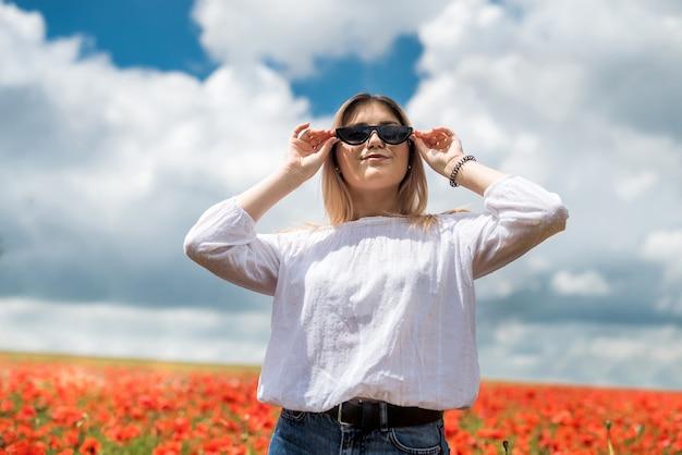 양 귀 비의 분야에서 흰 블라우스에 우크라이나어 젊은 아가씨. 여름 시간