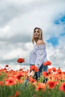 ポピーの分野で白いブラウスを着たウクライナの若い女性