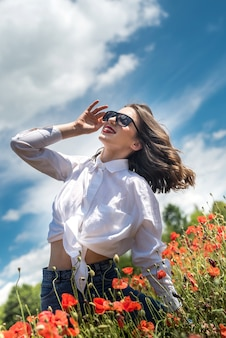 Ukrainian young  lady in white blouse in the field of poppies