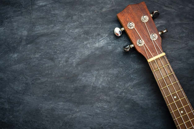 Ukulele on black cement. concept of hawaiian musical instruments and music lovers.