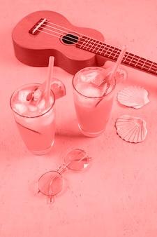 Ukulele; cocktail glasses; scallop seashells and sunglasses on coral background