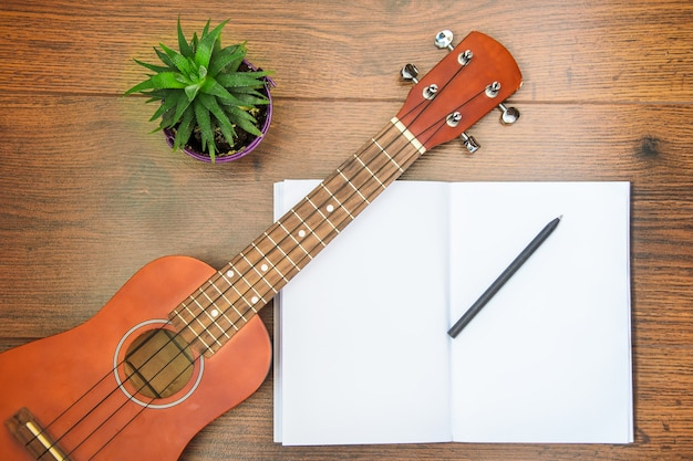 Ukulele four-string guitar on wooden table with a notebook and pen. concept of learning to play musical instrument, self-education.