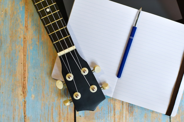 Ukulele fretboard and notepad on wooden table. independent online learning to play hawaiian guitar.