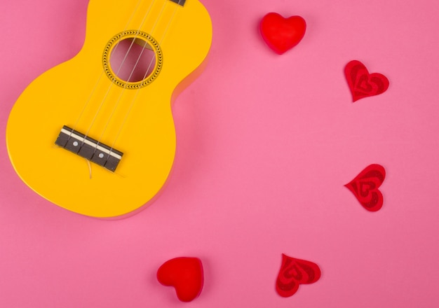 Ukulele guitar and red hearts forming a circle against a bright pink background (love song concept)