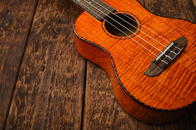 木の表面のウクレレハワイアンギターのクローズアップ