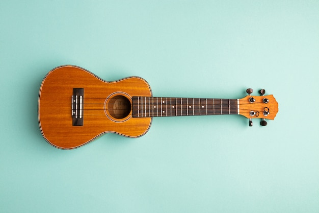 Ukulele isolated on abstract turquoise background with copy space. trendy musical instrument flat lay.