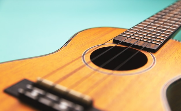 Ukulele macro perspective view with copy space. selective focus. turquoise background.