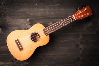 Ukulele on black wooden background. Acoustic music instrument. Top view.