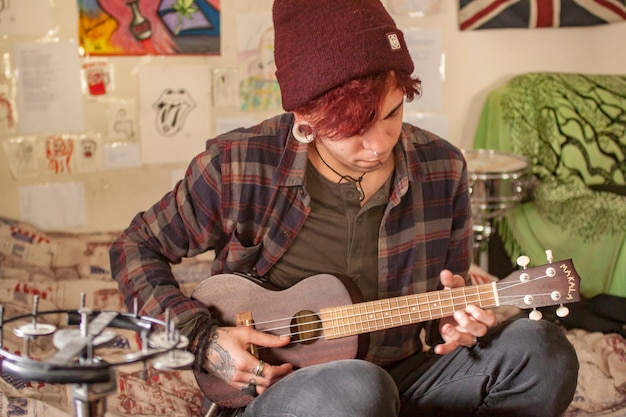 Ukulele player plays his instrument at home