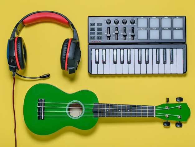 Ukulele and wired blue microphone on yellow background. the view from the top.