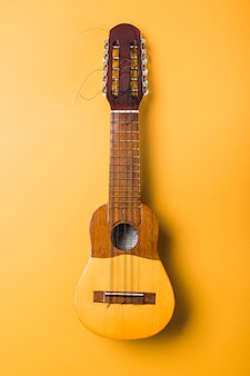 Ukulele with broken string on yellow background