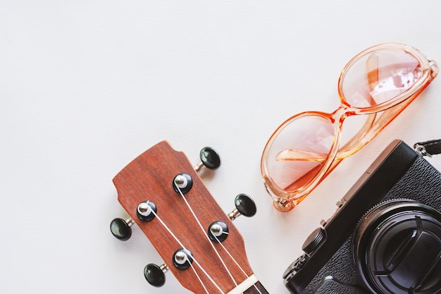 Ukulele with sunglasses and camera on white background for travel accessories