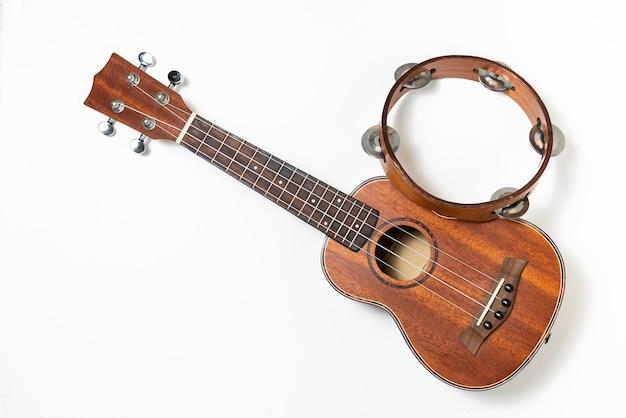 Ukulele and wooden tambourine on white