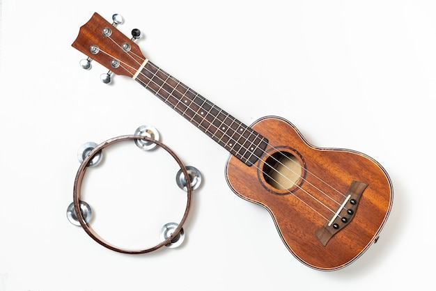 Ukulele and wooden tambourine on white