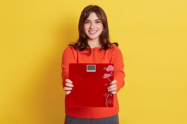 体重が減る。手に赤いフロアスケールを保持している若い魅力的な女性