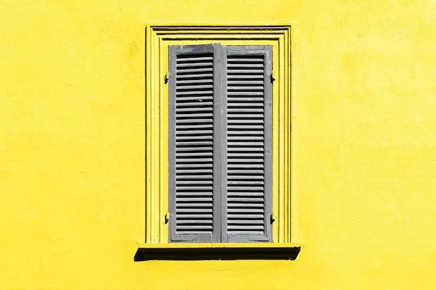 궁극적 인 회색과 밝은 노란색. 창에 회색 셔터