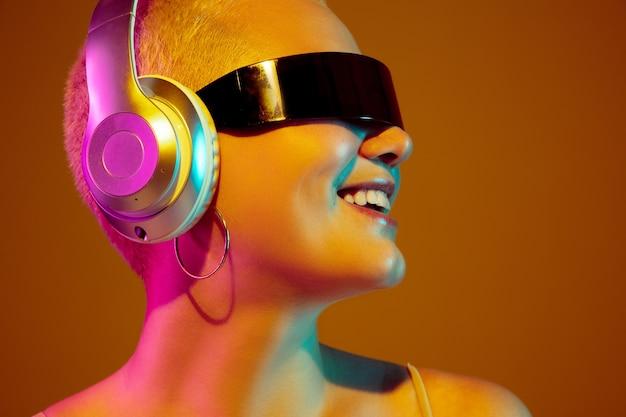 ウルトラテック、クローズアップ。ネオンの光の中で茶色の若い女性。ファッショナブルでトレンディなアイウェアを備えた美しい女性モデル。