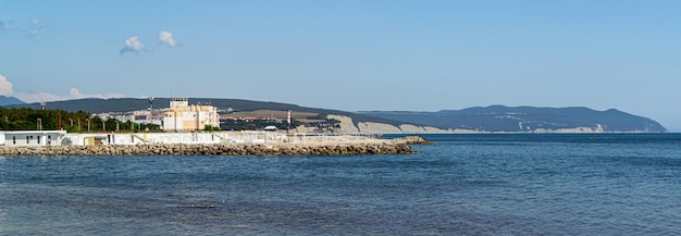 Ultra-wide panorama of the thin cape beach, a great place for camping, dense forest and beautiful seascape