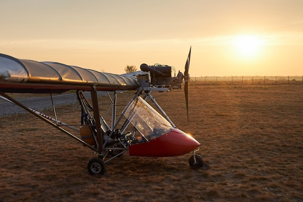 Ultralight single-engine single-seat aircraft stands on the airfield in the early morning