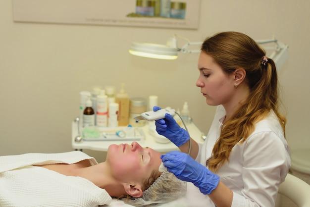 Ультразвуковой скребок. реальный снимок процедуры ультразвуковой чистки лица. косметологическая клиника. здравоохранение, клиника, косметология