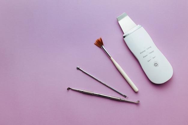 Ultrasonic scrubber, cosmetic peeling brush uno spoon lies on a purple background