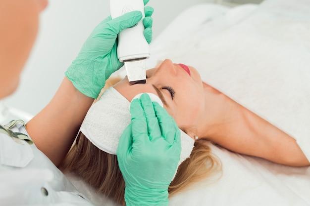超音波美容スクラバー顔のキャビテーション手順若い女性のクライアント美容クリニックはプロを取得します